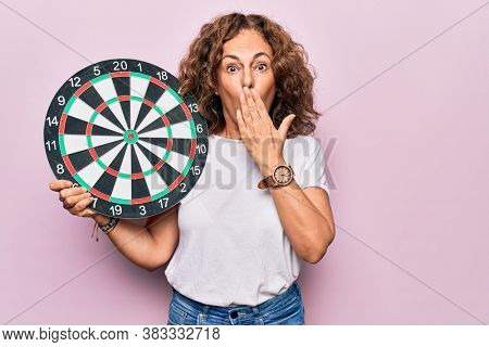 Middle age beautiful woman holding dartboard standing over isolated pink background covering mouth with hand, shocked and afraid for mistake. Surprised expression