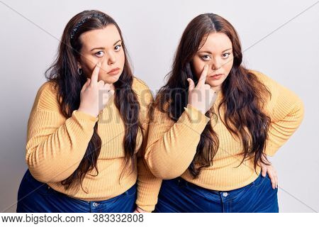 Young plus size twins wearing casual clothes pointing to the eye watching you gesture, suspicious expression