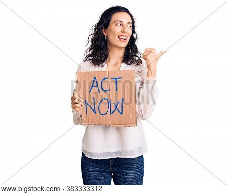 Young beautiful hispanic woman holding act now banner pointing thumb up to the side smiling happy with open mouth