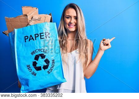 Young beautiful blonde woman recycling holding paper recycle bag full of paperboard smiling happy pointing with hand and finger to the side