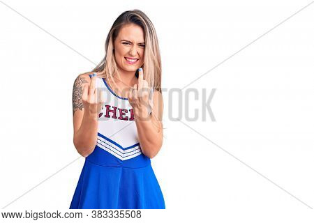 Young beautiful blonde woman wearing cheerleader uniform showing middle finger doing bad expression, provocation and rude attitude. screaming excited