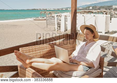 Young woman using laptop computer on a beach. Freelance work concept.