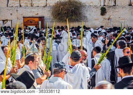 JERUSALEM, ISRAEL - SEPTEMBER 26, 2018: The area in front of Western Wall of Temple filled with people. The Jews of ritual clothes - tallit hold four ritual plants. Morning autumn Sukkot