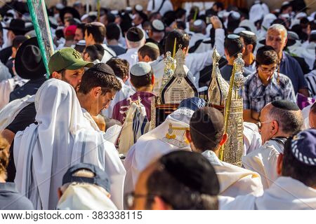 JERUSALEM, ISRAEL - SEPTEMBER 26, 2018: Religious Jews carry out sacred Torah Scrolls. The Jews, wrapped in tallits, pray at the Western Wall. Sukkot. Religious tourism concept