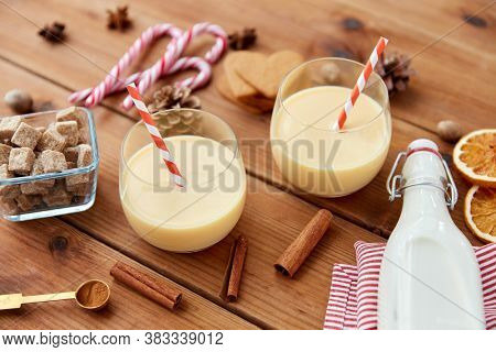 christmas and seasonal drinks concept - glasses with eggnog, ingredients and aromatic spices on wooden background