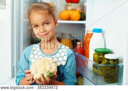 Little Girl Standing In Front Of A Fridge And Choosing Food