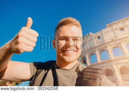 Happy Young Man Making Selfie Thumb Up Sign In Front Of Colosseum In Rome, Italy. Concept Travel Tri