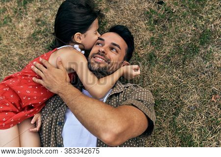Top View Of A Father Cuddling With His Daughter During Picnic Lying On The Grass Outdoors. Dad Enjoy