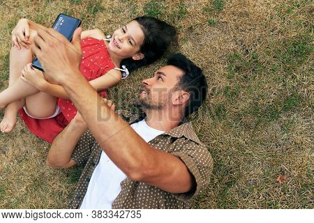 Father Playing On Smartphone With His Daughter During Relaxing On The Grass Outdoors. Dad Enjoying A