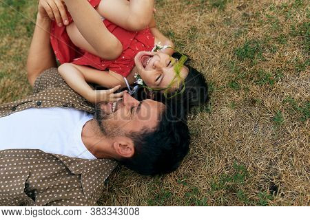 Smiling Father Playing With His Happy Daughter During Lying On The Grass Outdoors. Dad Enjoying At D