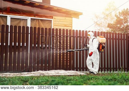 Disinfector In Protective Suit Processes Territory Of Garden Plot Of House Sprays Poison From Mosqui