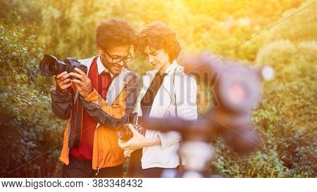 Photographer team with SLR camera and medium format camera taking pictures in nature