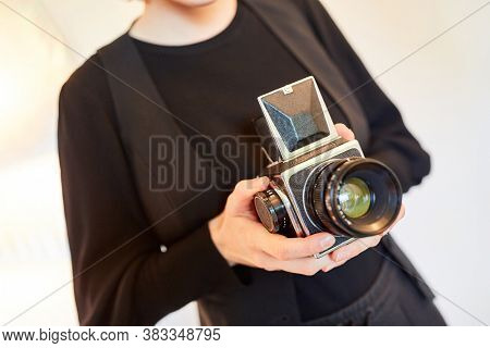 Photographer holds medium format camera or shaft camera with light shaft finder