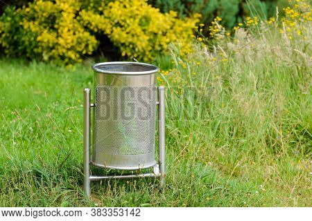 Metal Trash Can On A Green Lawn In A Park Close-up