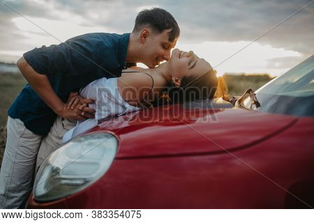 Young Couple In Love Kisses And Embraces On Red Car Bonnet In Meadow At Sunset.