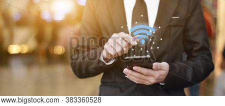 Businessman Hand Using Mobile Smartphone With Wifi Icon. Idea For Business Communication Social Netw