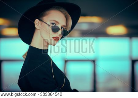 Fashionable young woman in black clothes and sunglasses in interiors. Beauty, fashion. Optics and eyewear.