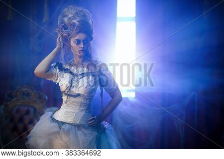 Vampires. Charming and terrible vampire woman against the background of light rays from the window in the old abandoned castle. Vintage style. Halloween.