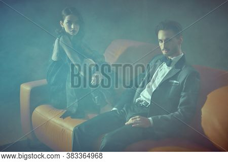 Beautiful elegant couple in fashionable evening clothes posing in smoky luxury apartment. Glamorous lifestyle. Fashion shot.
