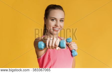 Sporty Lifestyle. Athlete Happy Woman Doing Dumbbell Boxing Cardio Workout Over Yellow Studio Backgr