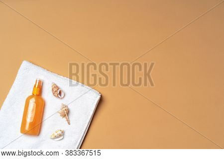 Suntan Oil Spray With Seashells On Beige Background