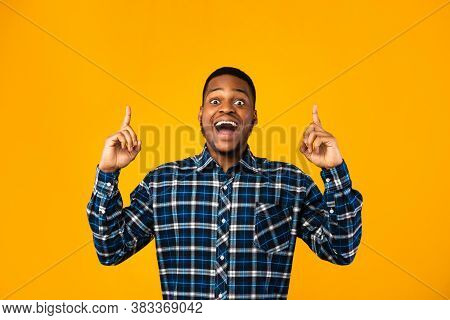 Look Up. Excited African American Guy Posing Pointing Fingers Upward Standing On Yellow Background.