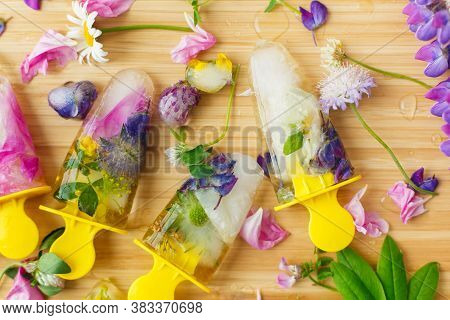 Hello Summer Concept. Floral Ice Pops Flat Lay. Colorful Wildflowers In Frozen Popsicles And Ice Cub