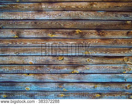 Background Of Brown Wooden Fence Made Of Planks. The Texture Of An Old Rustic Wooden Fence Made Of F