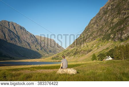 Scenic View Of Loch Achtriochtan In Glen Coe, Scottish Highlands, Uk. Back View Of An Unidentified M