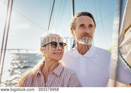 Portrait Of Two Senior People Looking Away. Mature Couple Standing On Yacht Enjoying Their Sailing T