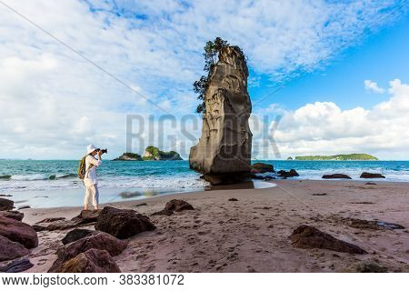 Ocean tide in the Cathedral Cove. Woman tourist taking pictures of beach. Mirror reflections of clouds in wet sand. Travel to New Zealand. The concept of exotic, ecological and photo tourism