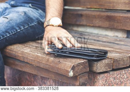 Hand Pulling A Wallet Forgotten On A Wooden Bench In A Park.