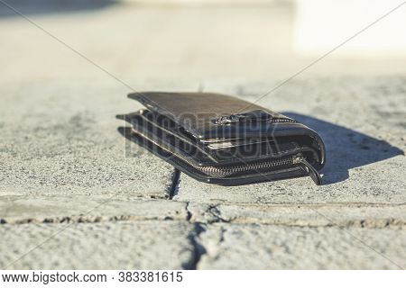 Black Wallet With Cash Is Lying Lost On Bench.