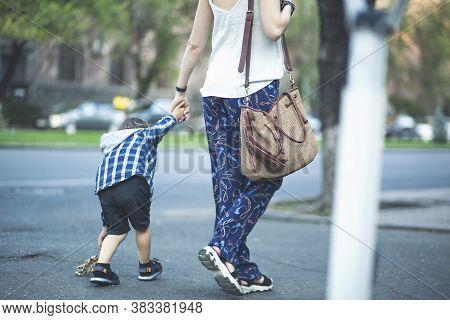 Mom And Child Walk Around The City.