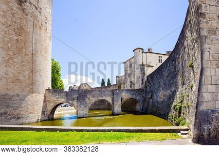 The historic tower of Constance. Powerful medieval walls and a moat with water surround the  city of Aigues-Mortes. Mediterranean coast of France. The concept of historical and photo tourism
