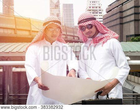 Arab Business Partners Team With Blueprint Looking Away, Arabic Business And Businessmen Working Tog