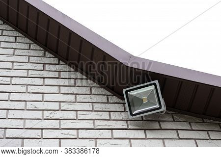 A Large Rectangular Led Floodlight Hangs Under The Roof On The Wall Of A Country House, Whose Walls