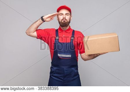 Give Salute Or Yes Sir! Young Confident Logistic Delivery Man With Beard In Blue Uniform And Red T-s