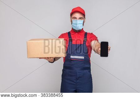 Young Man With Surgical Medical Mask In Blue Uniform And Red T-shirt Standing, Holding Cardboard Box