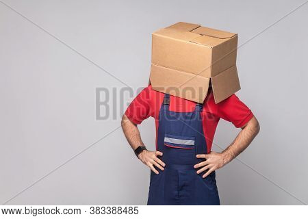 Portrait Of Young Logistic Delivery Man In Blue Uniform And Red T-shirt Standing And Covering Face W