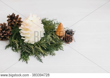 Christmas Pine Cone Candle And Tree In Rustic Christmas Wreath On White Wood. Small Pine Tree And Mo