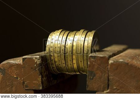 A Few Coins In A Metal Vise. Concept Of Economic Problems. Selective Focus