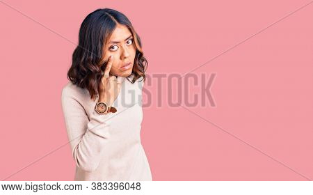 Young beautiful mixed race woman wearing winter turtleneck sweater pointing to the eye watching you gesture, suspicious expression