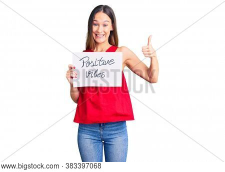 Beautiful brunette young woman holding positive vibes banner smiling happy and positive, thumb up doing excellent and approval sign