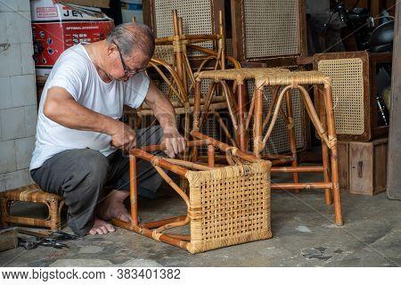 George Town, Penang/malaysia - Jul 19 2018: A Man Repair Ratten Chair.