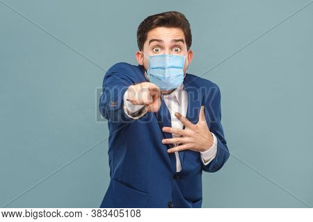 Shocked Man With Surgical Medical Mask Pointing Finger At Camera With Shocked Face.