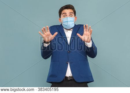 Portrait Of Afraid Young Shocked Man With Surgical Medical Mask. Looking At Camera With Scared Panic