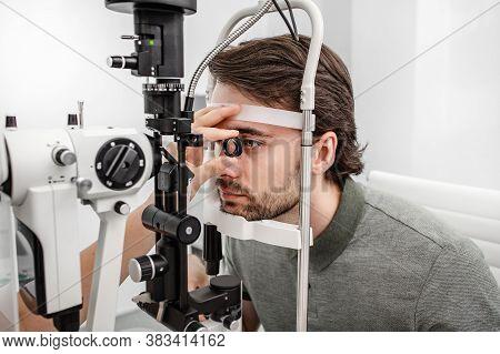 Adult Man Eyesight Test With Binocular Slit-lamp. Checking Retina Of A Male Eye Close-up. Ophthalmol