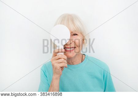Senior Woman Having An Eye Exam With One Eye Covering Using A Special Tool, On A White Background. E