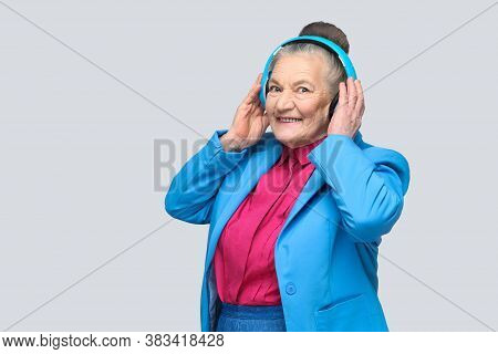 Trendy Happy Grandmother In Colorful Casual Style Holding Her Blue Headphones Listening And Enjoying